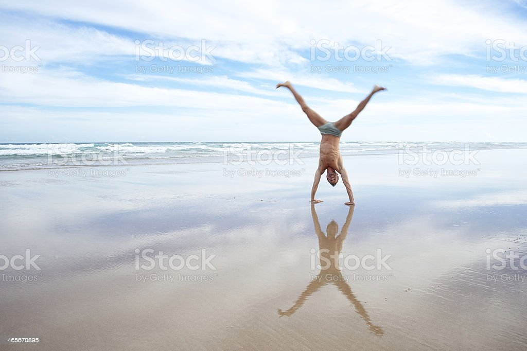 Man in Bathing Suit Does Cartwheel on Reflective Beach stock photo