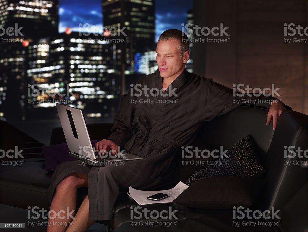 Man in bathrobe working on laptop at night stock photo