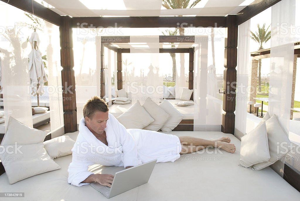 Man in Bathrobe Works at Luxury Desert Oasis stock photo