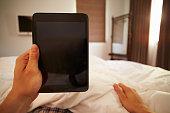 Man In Bed Looking At Digital Tablet
