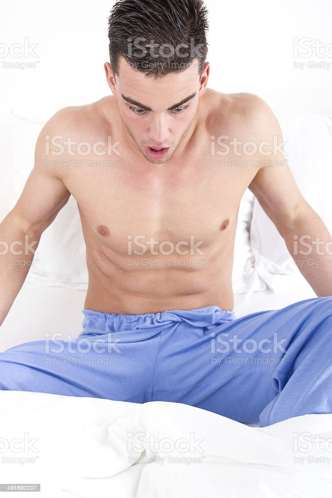 man in bed looking at his genital area having problems royalty-free stock photo