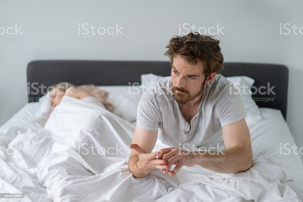 Man in bed looking upset stock photo
