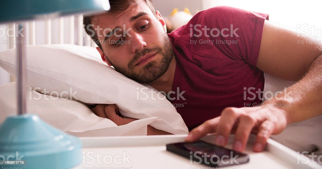 Man In Bed Woken By Alarm On Mobile Phone stock photo