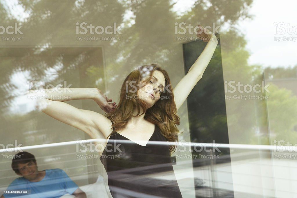 Man in bed, young woman stretching, eyes closed, view through window royalty-free stock photo