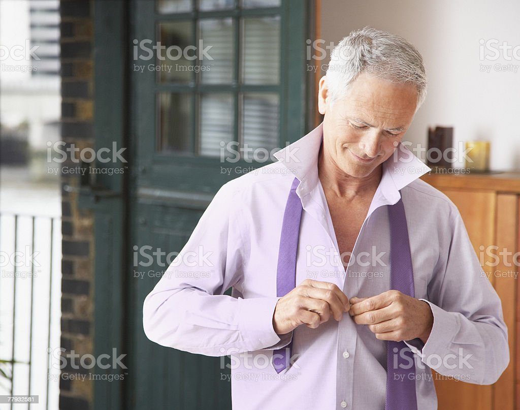 Man in bedroom getting dressed for work royalty-free stock photo