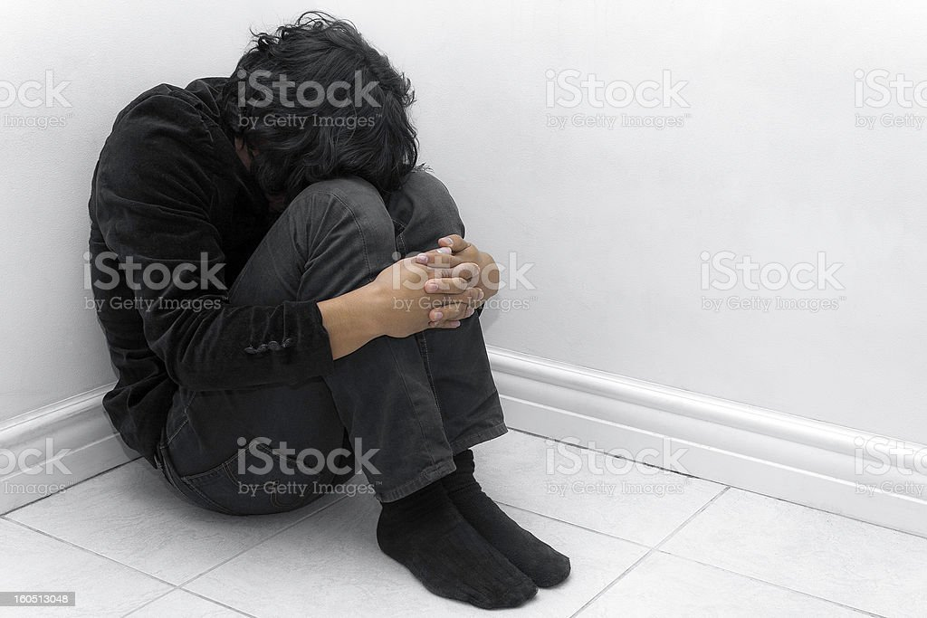 A man in black huddled in a corner stock photo