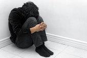 A man in black huddled in a corner