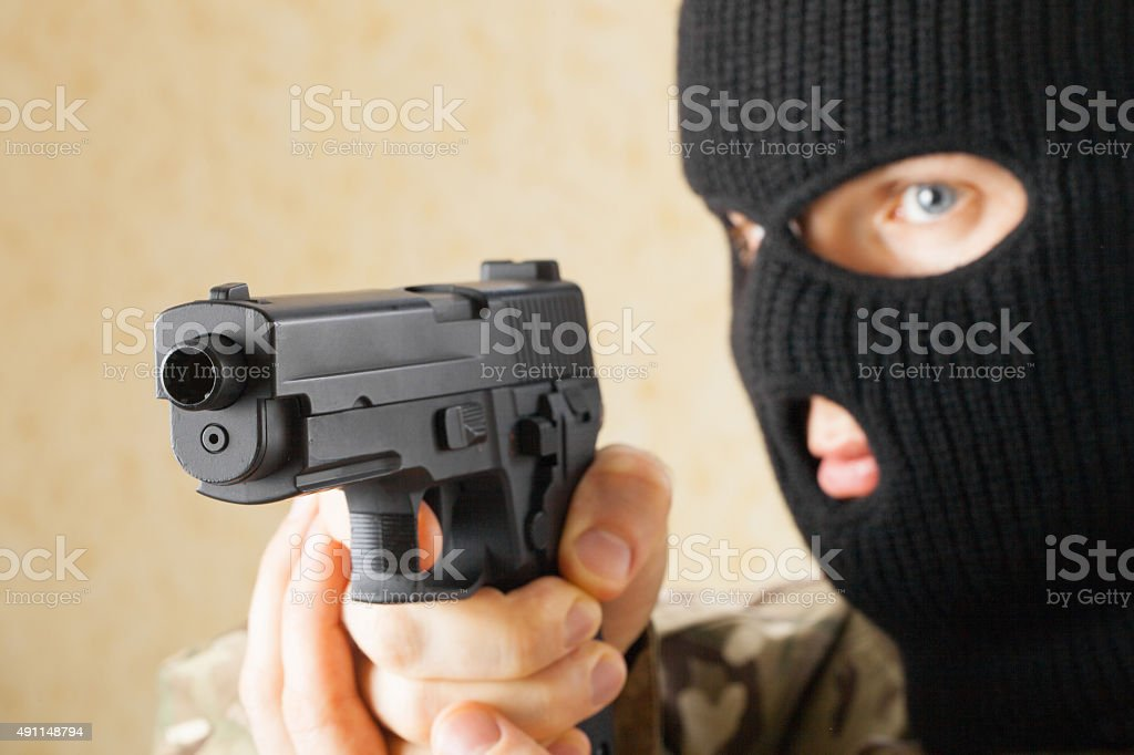 Man in black mask holding gun before him stock photo