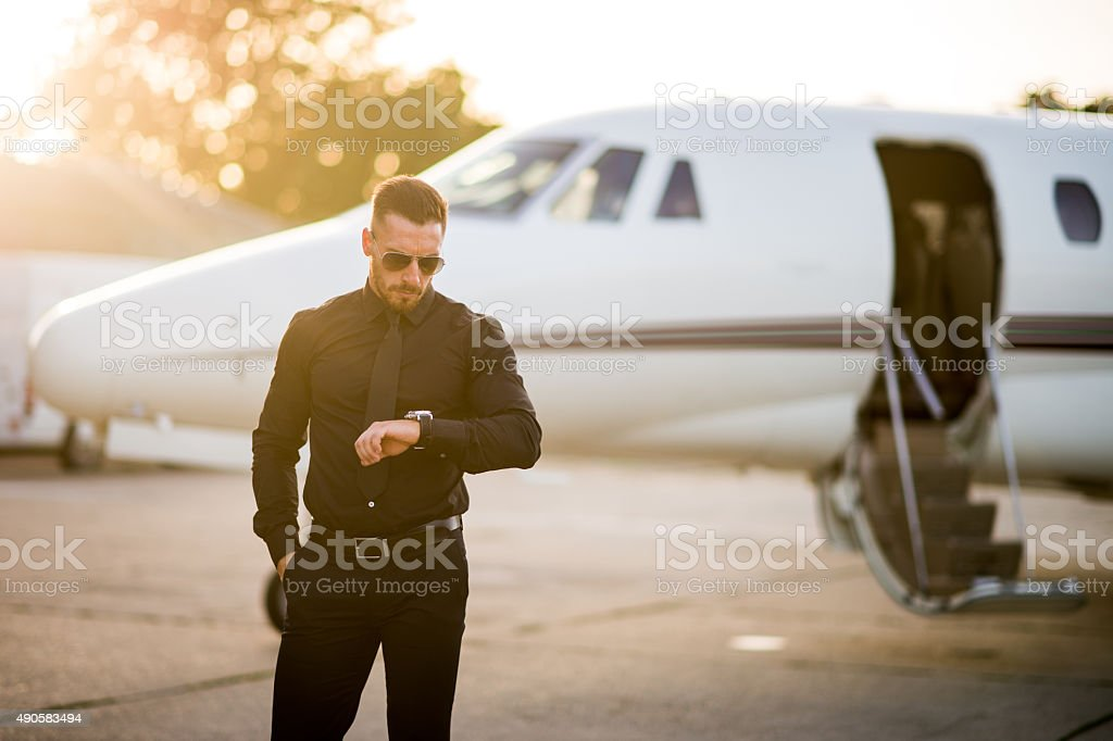 Man in black on the airport track stock photo