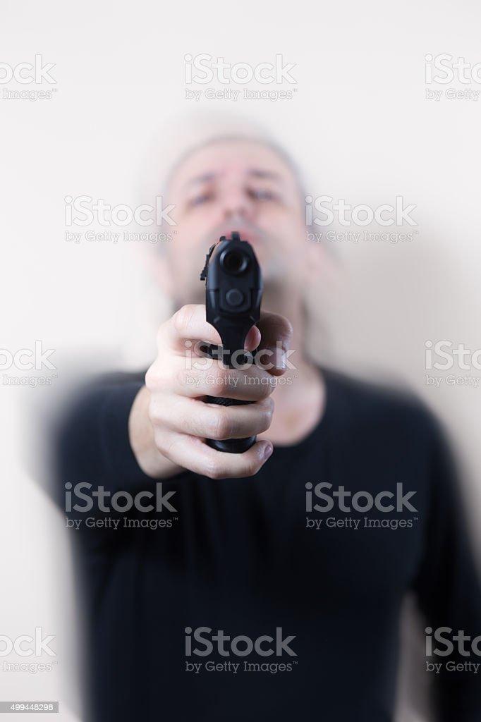 Man in black pointing handgun on White Background stock photo