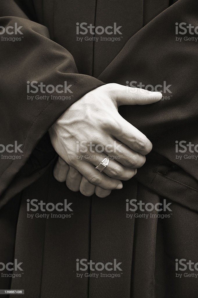 Man in black robe with crossed hands royalty-free stock photo
