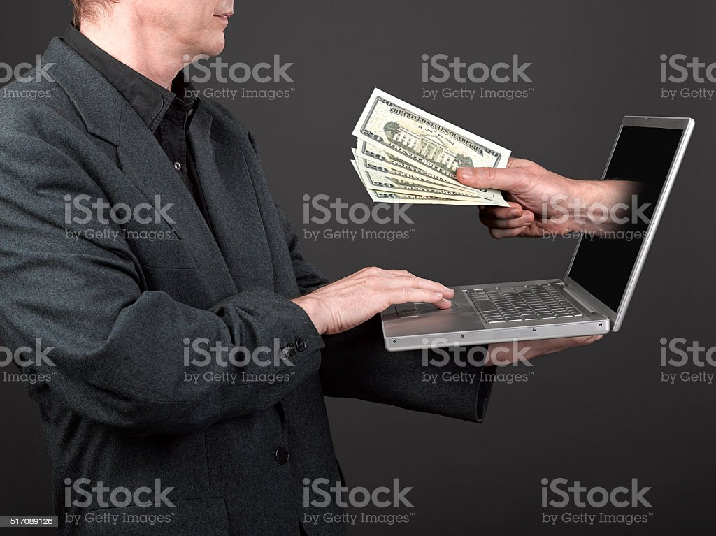 Man in black shirt and suit holding a laptop stock photo