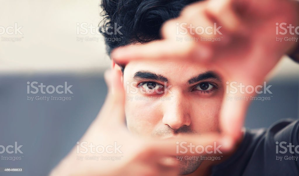 Man in black shirt forming square with hands for frame shot stock photo