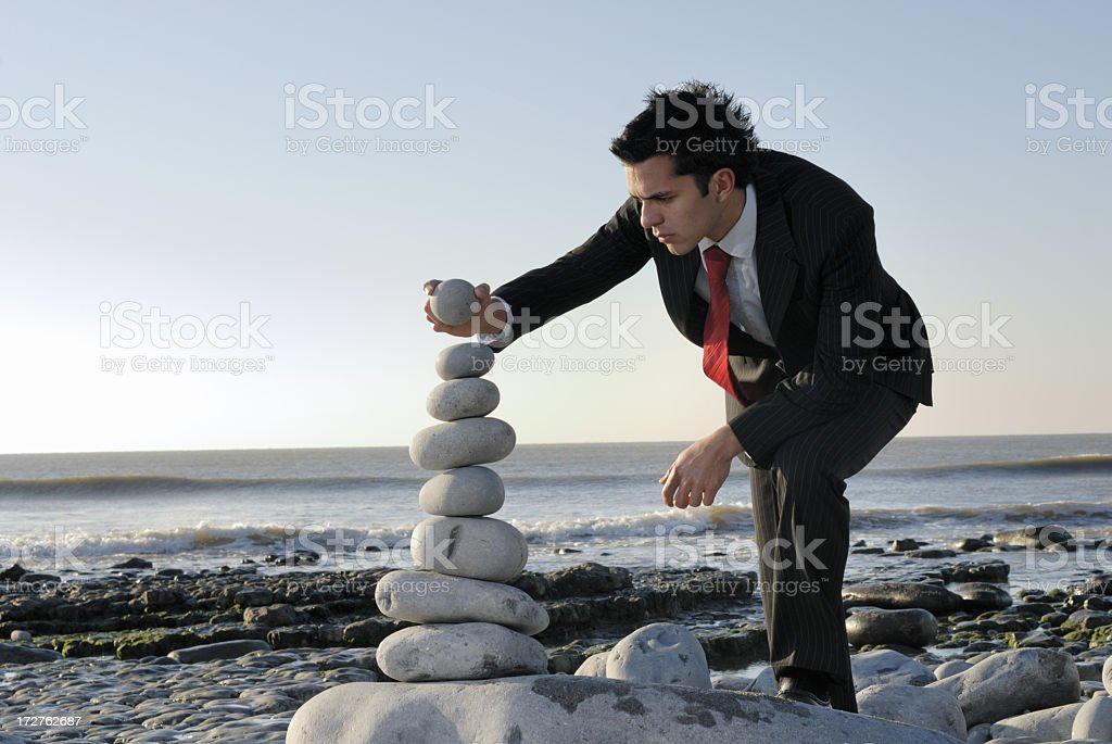 A man in black suit and red tie balancing rocks on beach royalty-free stock photo