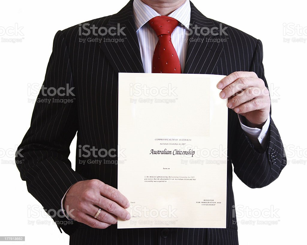 Man in black suit holding Australian Citizenship Certificate stock photo