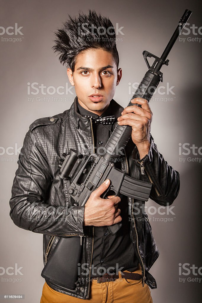 Man in black suit holding gun. stock photo