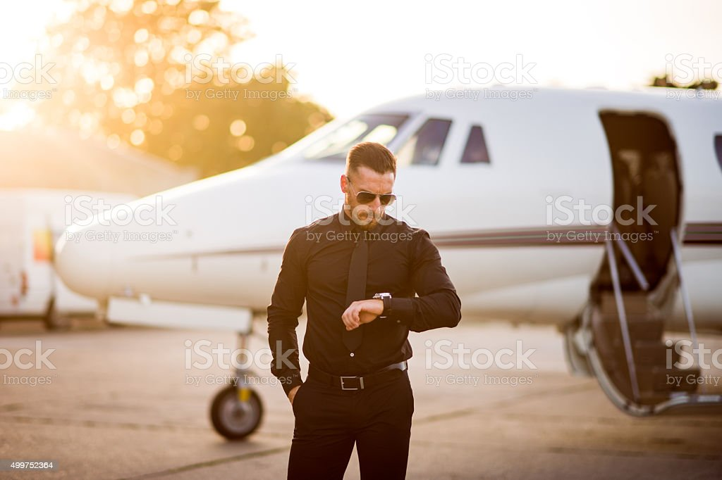 Man in black suit looking at his watch stock photo