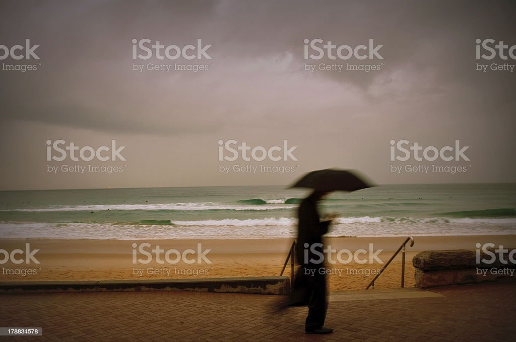 Business Man with Umbrella walking near beach stock photo