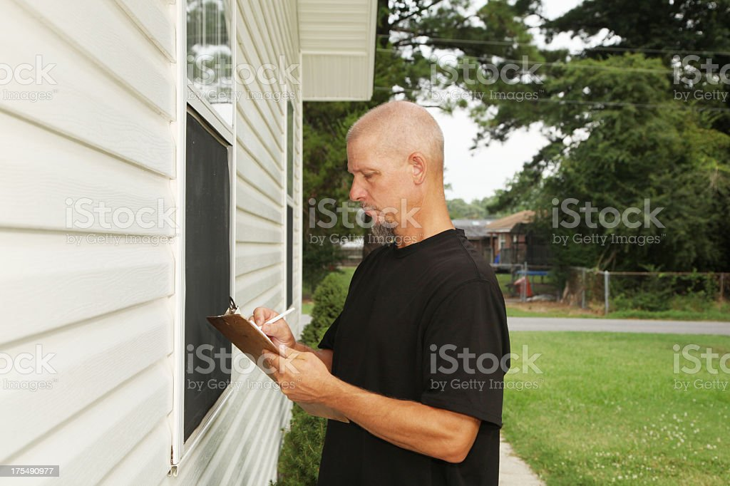 Man in black T-shirt writing on clipboard outside home stock photo