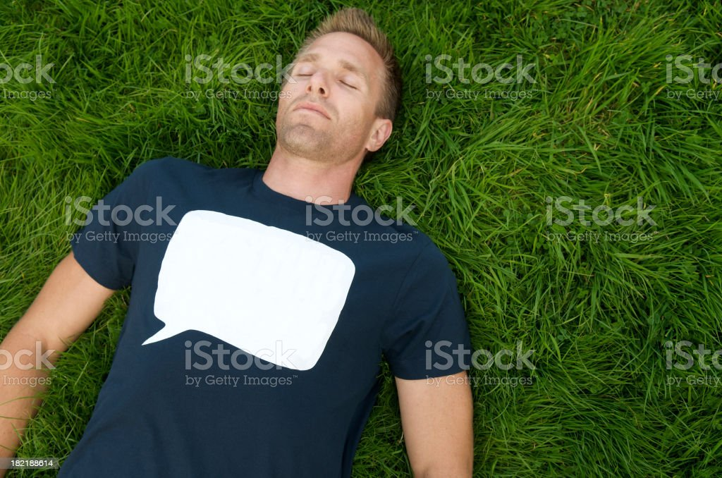 Man in Blank Speech Bubble Message Tee Napping Green Grass royalty-free stock photo