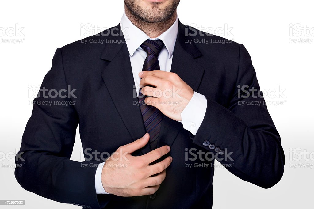 Man in blue dress adjusting his blue tie stock photo