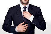 Man in blue dress adjusting his blue tie