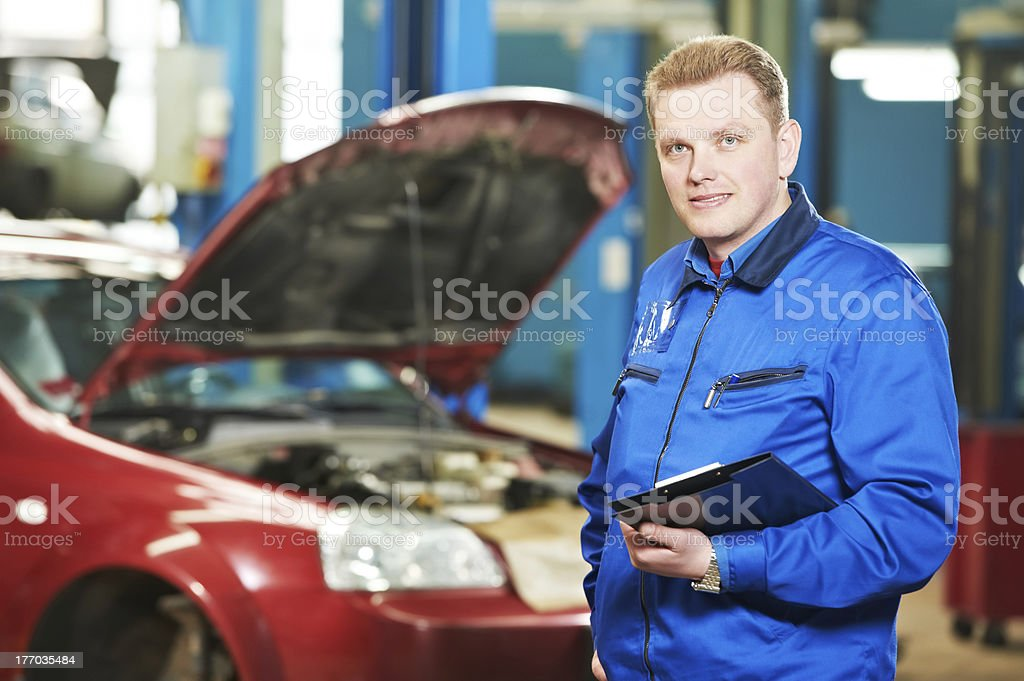 Man in blue jacket holding a notebook in front of a red car royalty-free stock photo