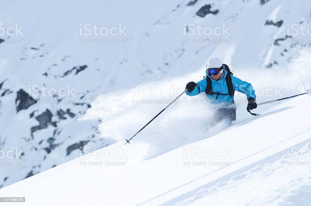 Man in blue outfit skiing in the snow at a rapid rate royalty-free stock photo