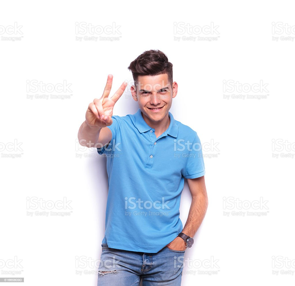 man in blue polo shirt showing the victory sign stock photo