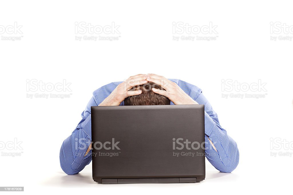 Man in blue shirt bending over a laptop and holding his head stock photo