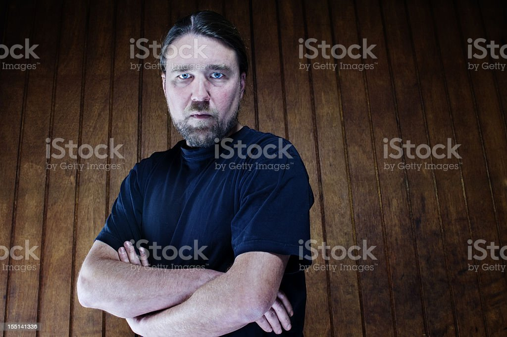 Man in blue shirt gazes intently with arms crossed royalty-free stock photo