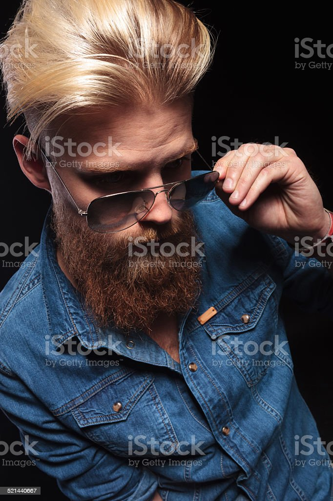 man in blue shirt looking down and fxing his sunglasses stock photo