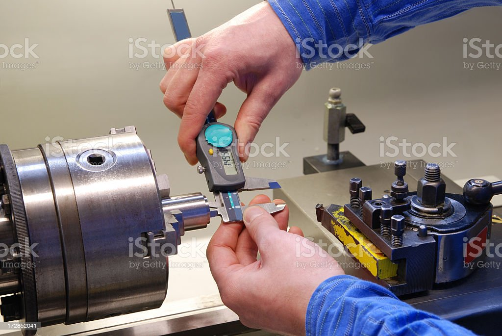 Man in blue shirt measuring parts with a digital caliper stock photo