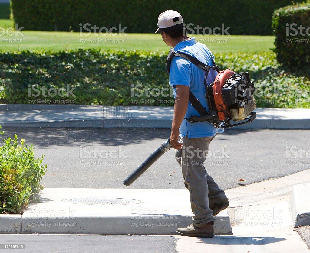 Man in blue shirt using a leaf blower on a sidewalk stock photo