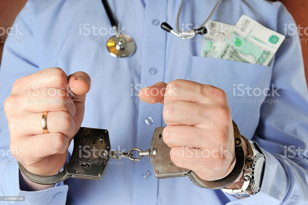 Man in blue shirt with money in his pocket and stethoscope royalty-free stock photo