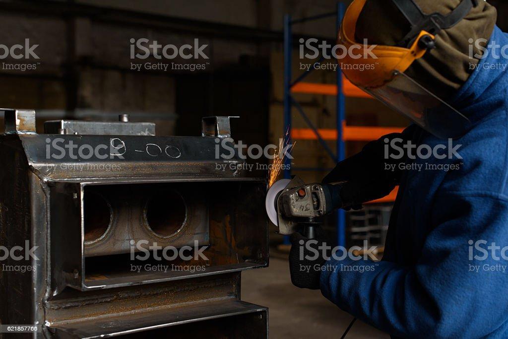 Man in blue solders black solid fuel boiler stock photo