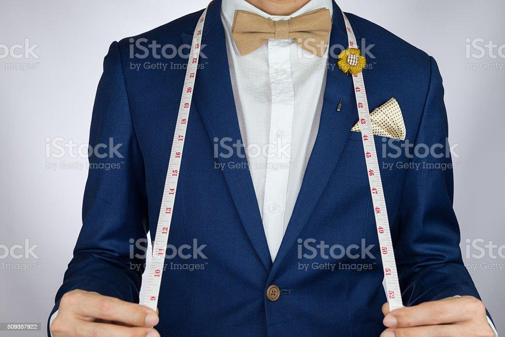 man in blue suit bowtie, brooch, pocket square blue suit stock photo