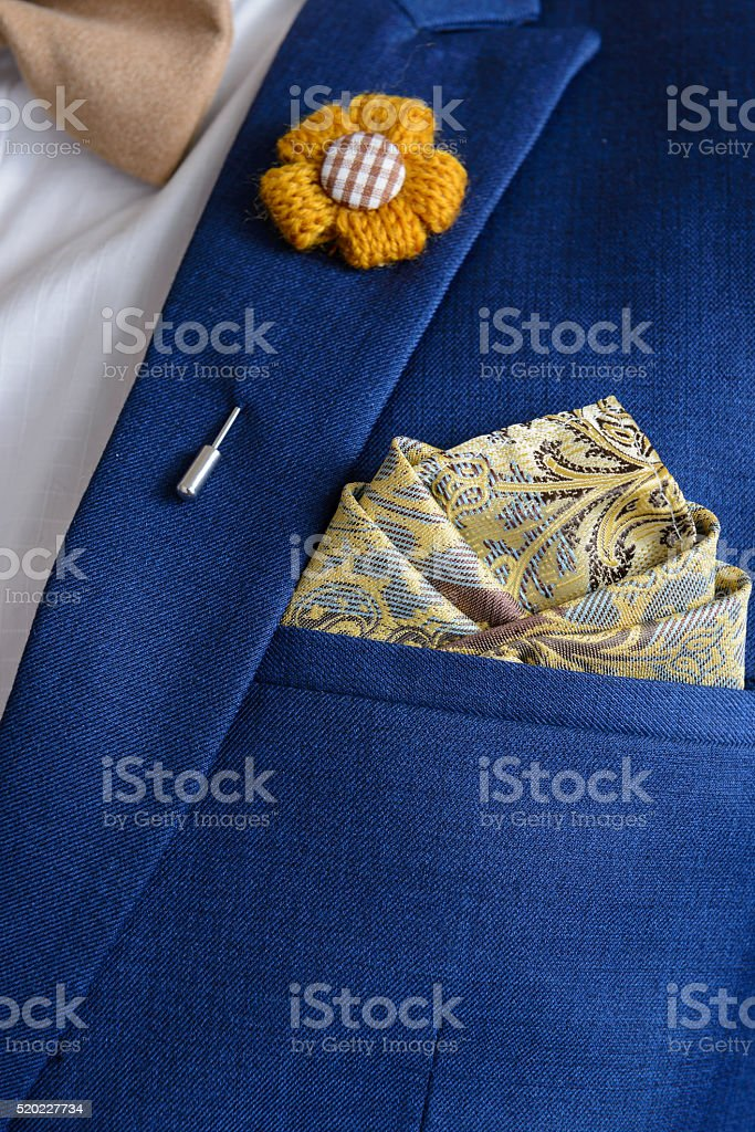 Man in blue suit with brown bow tie, flower brooch, and classic...