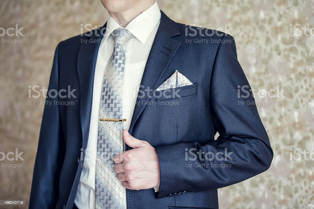 Man in blue suit with tie, tie clip and handkerchief stock photo
