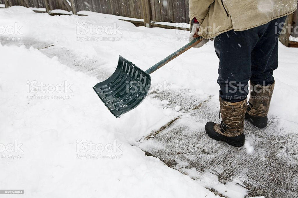 A man in boots shoveling snow from a sidewalk stock photo