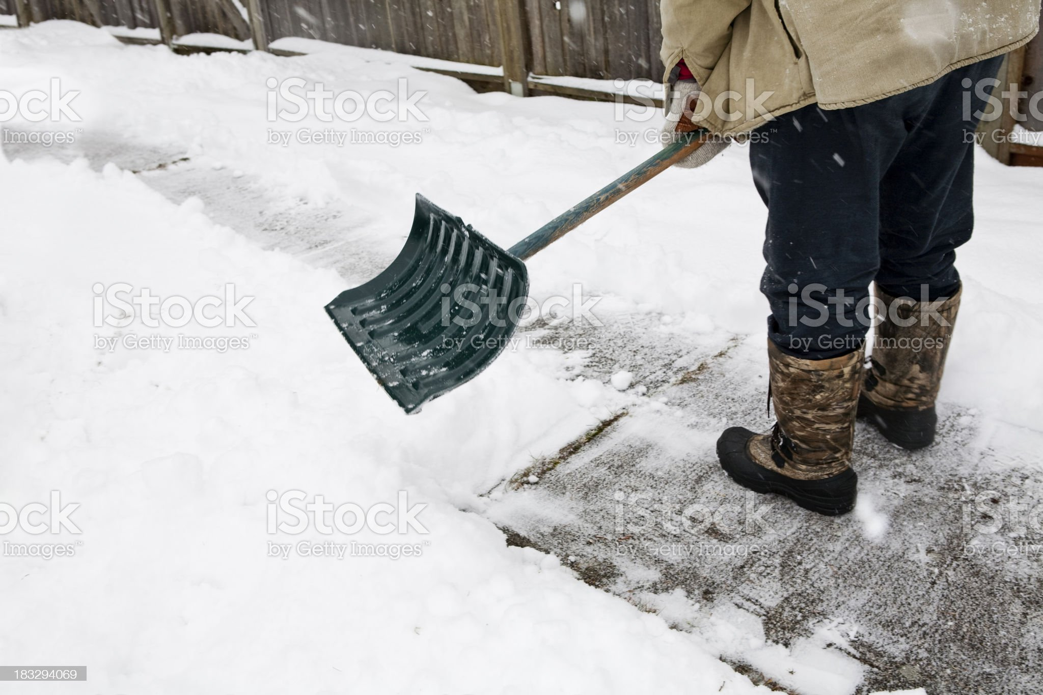 A man in boots shoveling snow from a sidewalk royalty-free stock photo