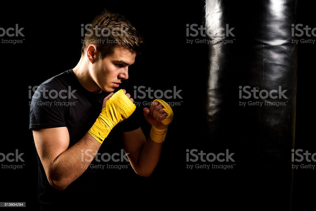 Man in boxing wraps is training and hitting heavy bag. stock photo