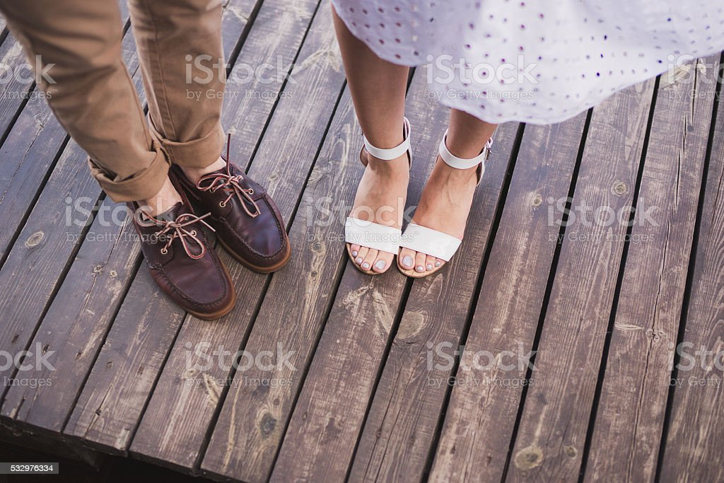 man in brown leather shoes and woman in white sandals stock photo
