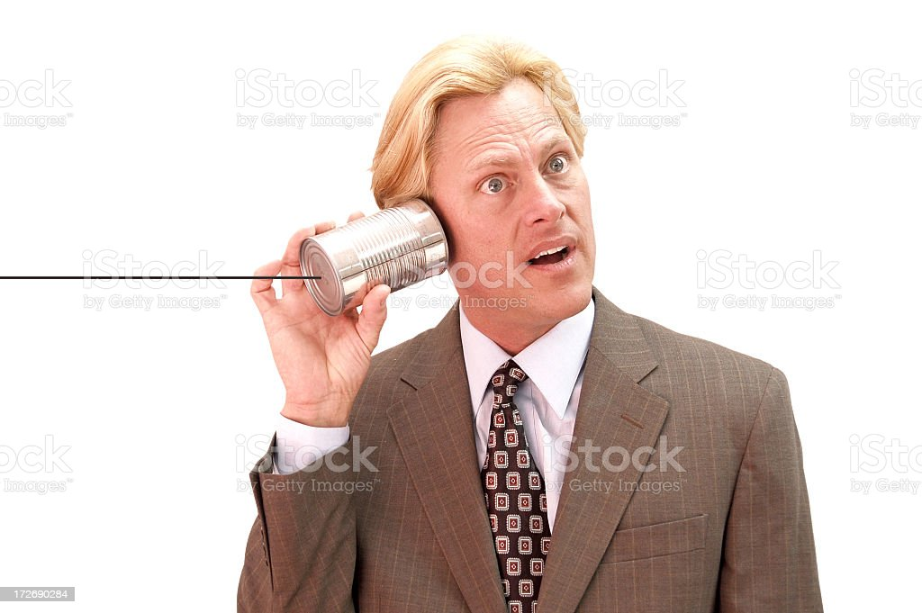 Man in brown suit with aluminum can to his ear stock photo