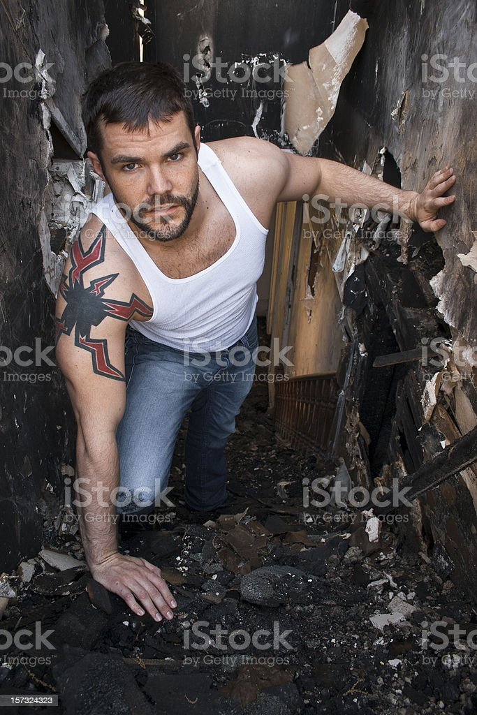 Man in Burnt Down House Climbing stairs. royalty-free stock photo
