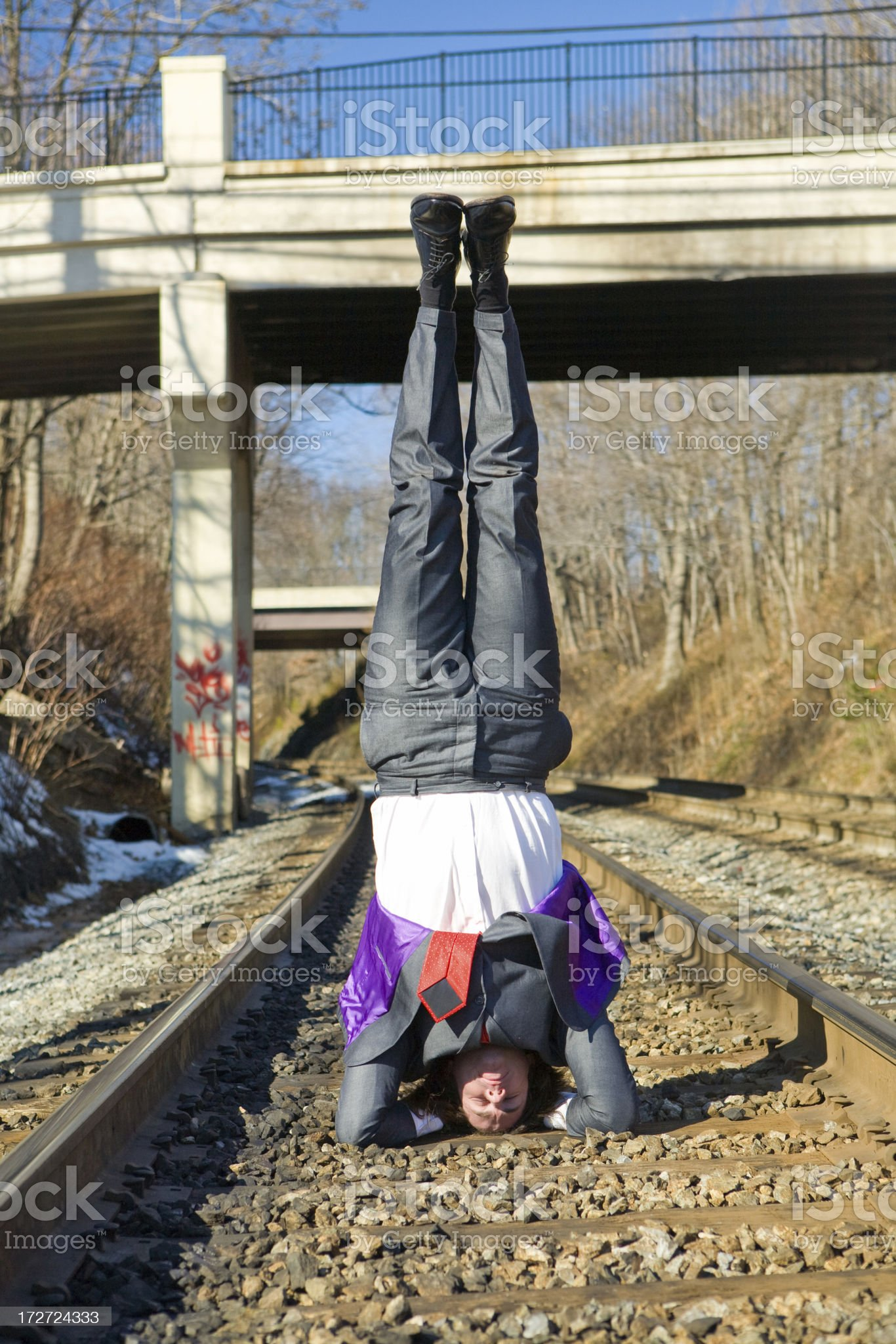 man in business suit does headstand on train tracks royalty-free stock photo