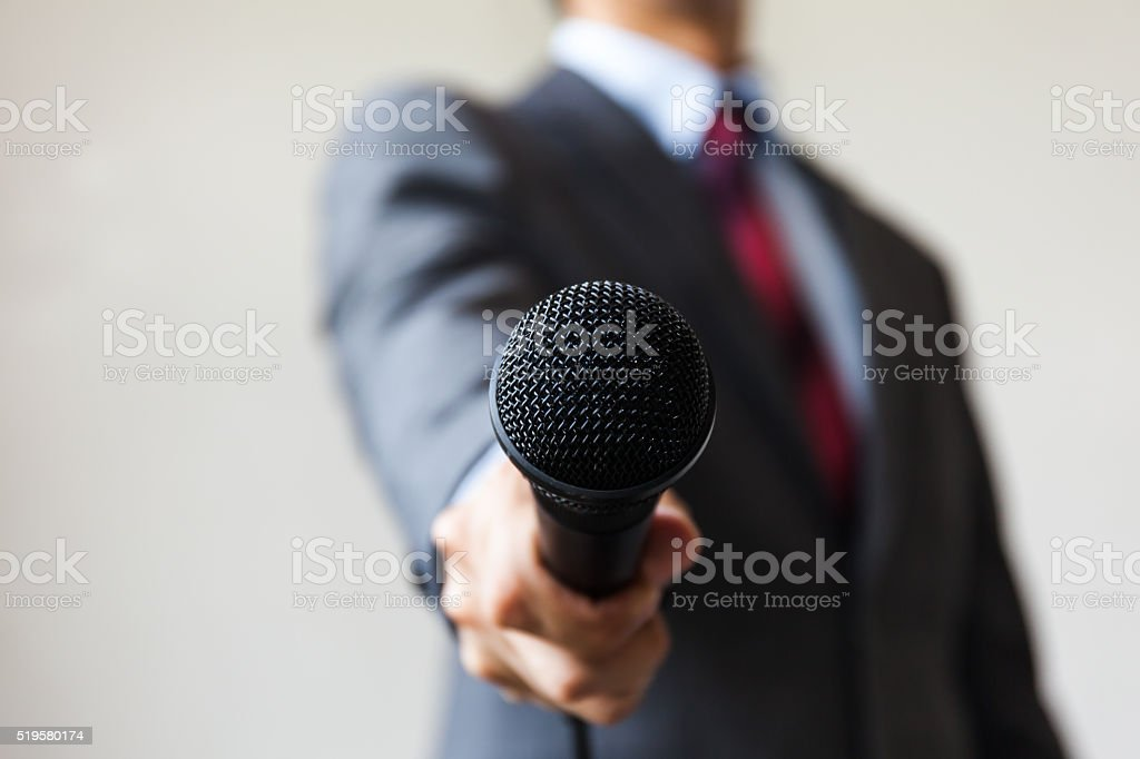 Man in business suit holding a microphone conducting a business stock photo