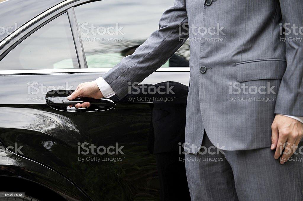 Man in business suit opening car door stock photo