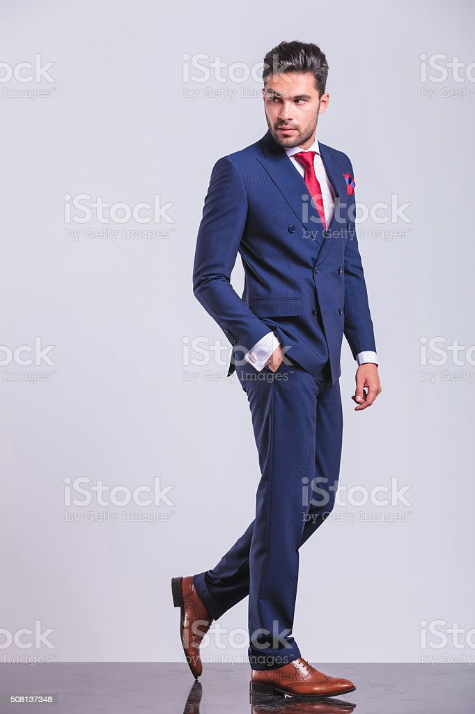man in business suit walking while looking away stock photo