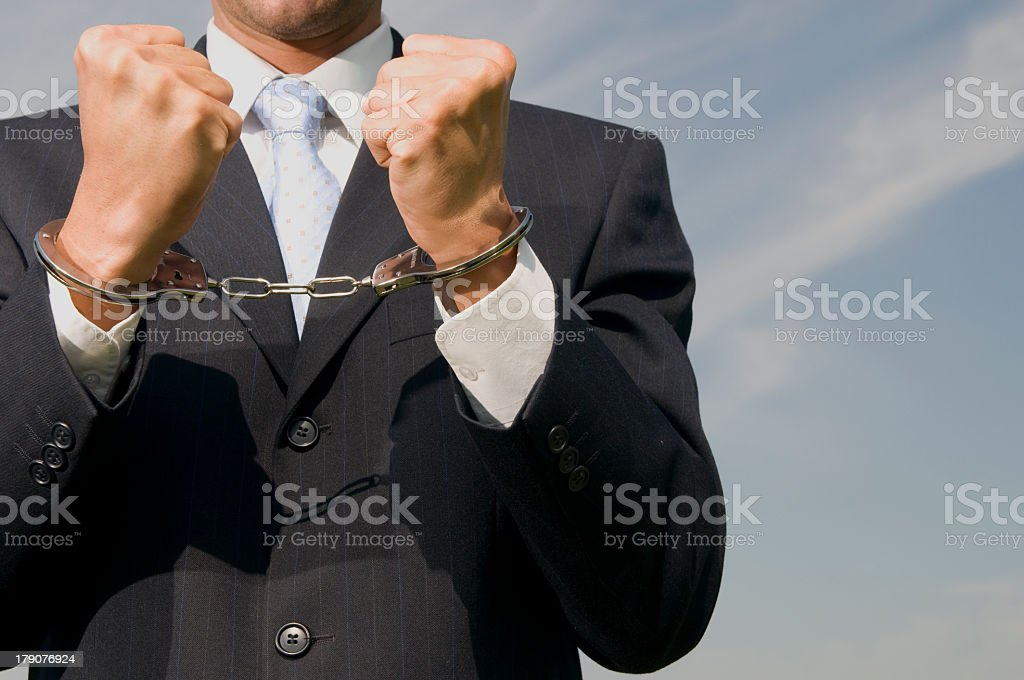 Man in business suit wearing handcuffs stock photo